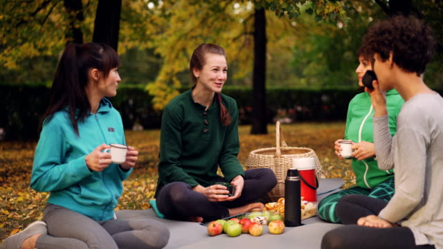 Cheerful-young-women-are-resting-on-mats-having-picnic-talking-and-drinking-tea-after-yoga-class-outdoors-on-beautiful-autumn-day-Food-and-basket-are-visible-
