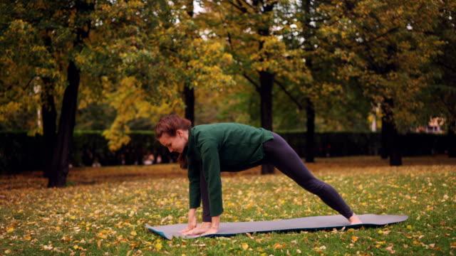 Fröhliche-Junge-Frau-tut-Yoga-Gleichgewichtsübungen-im-individuellen-Training-im-Stadtpark-auf-der-Matte-stehen-und-genießen-Sie-Ruhe-und-Natur-Menschen-und-Sport-Konzept-