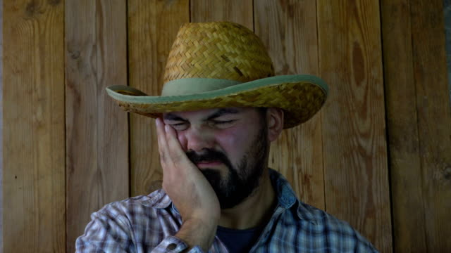 Unshaven-man-in-a-straw-hat-suffers-from-toothache