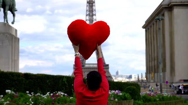 Mujer-joven-girando-alrededor-frente-a-torre-de-Eiffel-con-corazón-rojo-en-sus-manos-en-cámara-lenta-180-fps