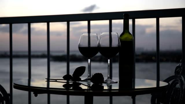 Noche-romántica-con-vino-tinto-en-el-balcón-al-atardecer