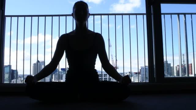 Silueta-de-mujer-sentada-en-suelo-meditar