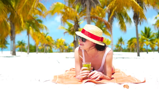 Young-beautiful-woman-relax-with-cocktail-on-white-tropical-beach