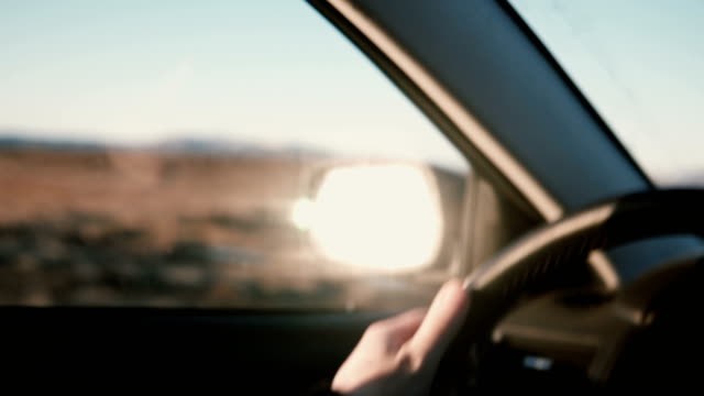 View-inside-the-car-on-countryside-desert-road-inbeautiful-sunset-Close-up-view-of-male-hands-on-wheel