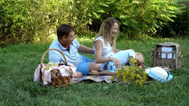 Happy-family-resting-in-nature-Dad-mom-and-little-son-sitting-playing-and-laughing-on-the-grass-in-the-Park-on-the-green-background-Family-picnic-outdoors-