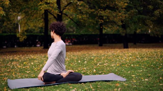 Chica-apuesta-en-deportes-ropa-es-torcer-su-cuerpo-sentado-en-posición-de-loto-y-luego-relajarse-con-ojos-cerrados-después-de-la-práctica-en-el-parque-en-día-de-otoño-