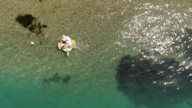 Aerial-view-of-two-women-floating-on-inflatable-in-Panagopoula-Greece-