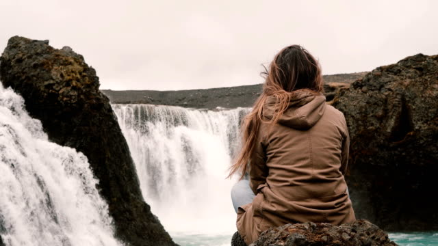 Back-view-of-young-pensive-woman-sitting-on-a-rock-alone-and-looking-on-powerful-waterfall-in-Iceland