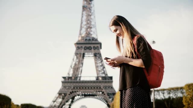 Hermosa-joven-con-mochila-de-pie-cerca-de-la-Torre-Eiffel-y-usando-el-teléfono-inteligente-navegar-por-Internet
