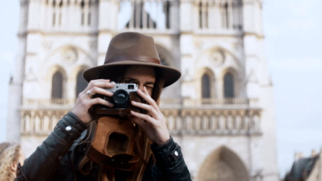 Portrait-of-young-smiling-woman-standing-near-the-Notre-Dame-cathedral-and-taking-photos-on-film-camera-in-Paris-France