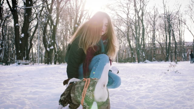 Young-woman-playing-with-Jack-Russell-terrier-in-winter-time-in-snow-slow-motion