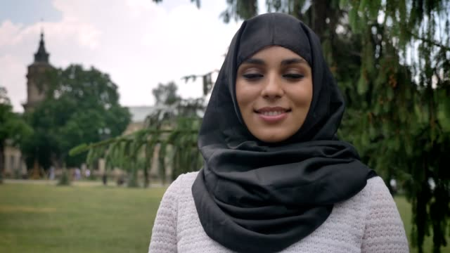 Young-muslim-woman-in-hijab-is-smiling-in-daytime-in-park-in-bad-weather-watching-at-camera-building-on-background-religiuos-concept