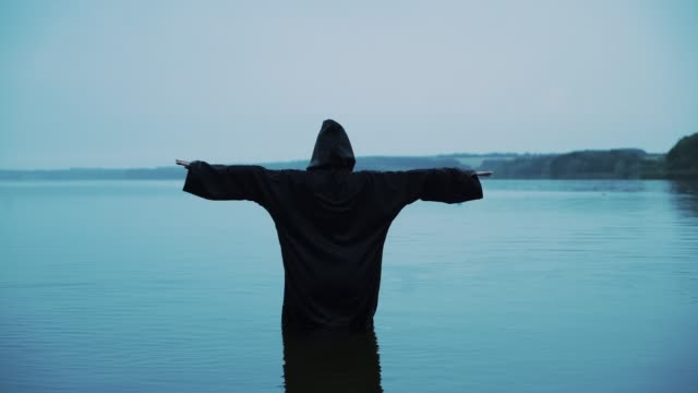 Scary-figure-in-black-mantle-in-the-river-