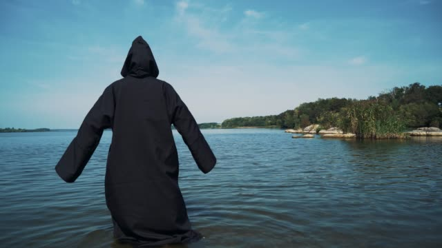Terrible-witch-in-black-mantle-in-the-water-outdoor-