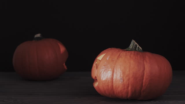Two-halloween-pumpkins-with-scary-face-on-the-wooden-table