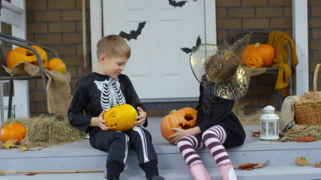 Little-Brother-and-Sister-in-Halloween-Costumes-Playing-with-Pumpkins