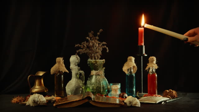 Lighting-candlestick-on-table-with-witchcraft-objects