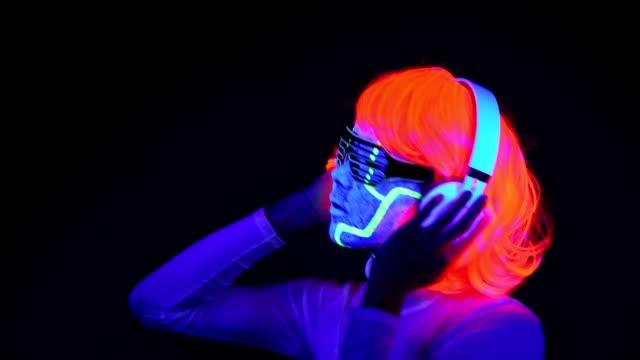 Mujer-con-pintura-Ultravioleta-de-la-cara-de-cyborg-peluca-brillantes-gafas-ropa-bailando-y-escuchando-música-con-auriculares-Mujer-asiática-