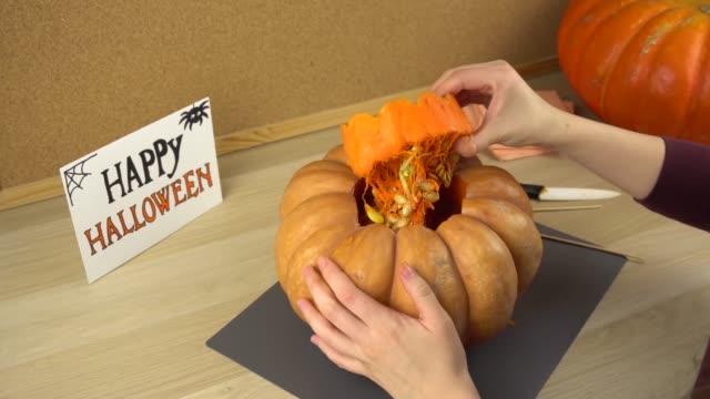 Mujeres-manos-tirón-de-la-tapa-y-hacen-un-agujero-en-la-calabaza-de-Halloween