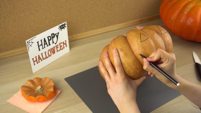 Women-s-hands-draw-a-face-on-a-pumpkin-for-Halloween-using-black-felt-tip-pen