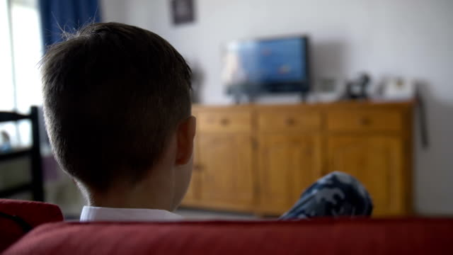 boy-sits-on-the-sofa-in-front-of-the-TV-and-switches-the-channels