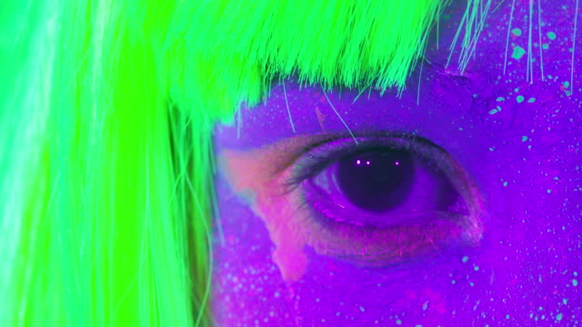 Closeup-woman-eyes-with-fluorescent-make-up-in-green-wig-creative-makeup-look-great-for-nightclubs-Halloween-party-shows-and-music-concept---slow-motion-video