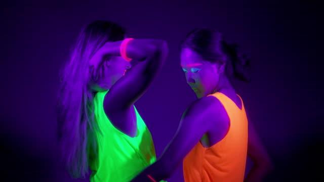 Lento-motin-de-hermosas-mujeres-sexy-con-maquillaje-fluorescente-y-ropa-de-baile-en-la-luz-de-neón-Club-nocturno-concepto-del-partido-