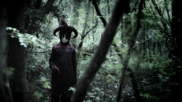 4k-Halloween-Shot-of-a-Child-in-Joker-Costume-Standing-in-Forest