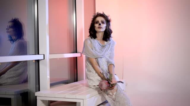 Cerca-de-una-joven-vestida-de-blanco-vestido-de-novia-con-creativas-hacen-de-halloween-espeluznante-y-aterrador-novia-muerta-de-aspecto-extraño-se-sienta-en-el-Banco-cerca-de-la-ventana