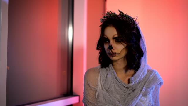 Cerca-de-la-cara-una-chica-joven-con-arte-de-cráneo-máscara-muerta-de-ella-la-novia-creativa-aterrador-y-escalofriante-halloween-hacer-está-sentado-mirando-la-ventana-el-Banco-del-fondo-rosa