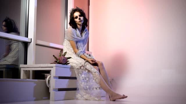 Chica-joven-en-vestido-blanco-y-velo-de-participar-en-la-fiesta-de-halloween-sentado-en-la-sala-con-maquillaje-espeluznante-miedo-creativo-está-en-el-Banco-cerca-de-la-ventana-aspecto-de-la-flor