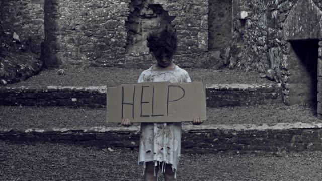 "4k-Horror-Shot-of-an-Abandoned-Child-Holding-""Help""-on-cardboard"