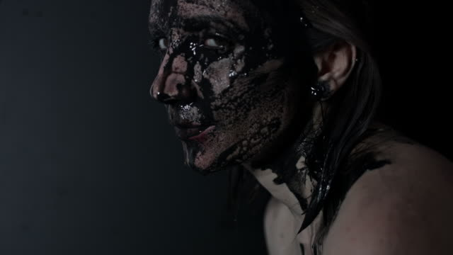 4k-shoot-of-a-horror-Halloween-model---Woman-washing-black-mud-and-smiling