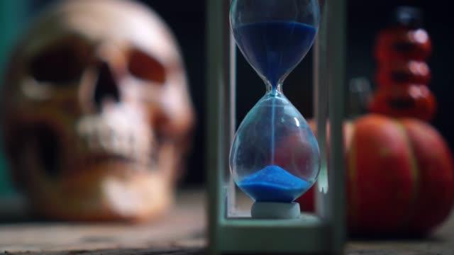 Halloween-sandglass-with-human-skull-and-pumpkin