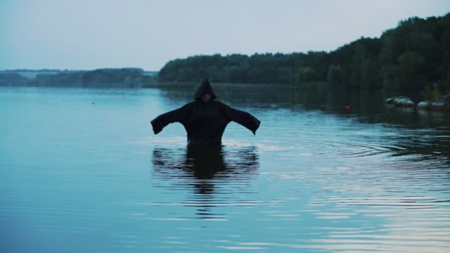 Evil-witch-in-black-cloak-with-hood-in-the-river-