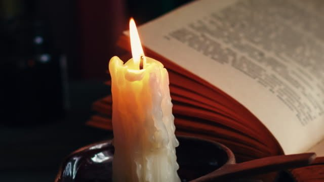 Time-lapse-candle-and-old-books-at-night-time-Close-up-view-Cinematic-color-grading-