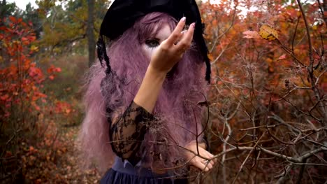 Young-pink-hair-witch-in-hat-search-reagents-in-the-mystical-autumn-forest-Halloween-preparation-