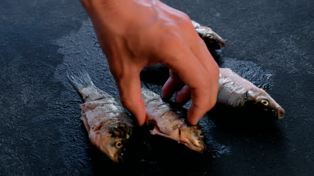 Man-turns-the-carps-fish-on-the-table-and-sprinkles-it-with-spices-Cooking-fish-Hand-close-up-