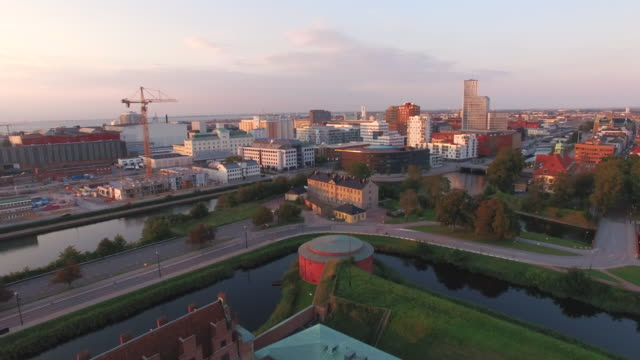 """Aerial-view-flying-over-Malmo-city-at-sunset-Drone-shot-of-""""Malmohus""""-in-Sweden-construction-site-and-cityscape-in-the-background"""