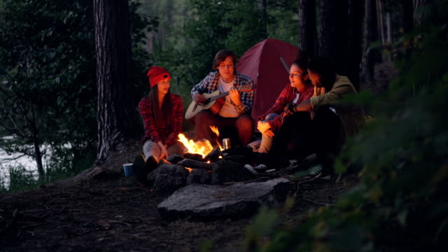Girls-and-guys-friends-are-singing-songs-while-guitarist-is-playing-musical-instrument-sitting-near-fire-in-forest-and-enjoying-nature-and-music-Tent-and-lake-are-visible-