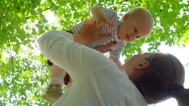 Happy-Mother-Lifting-and-Kissing-Baby-in-Park