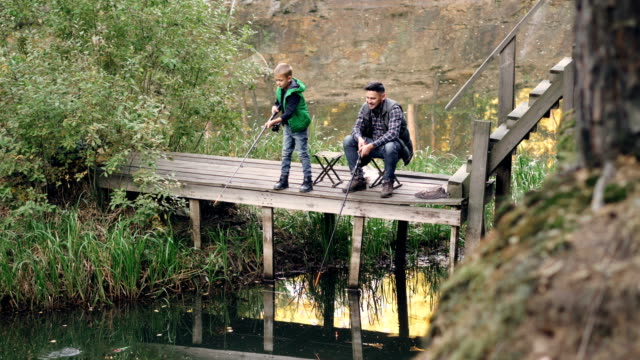 Chico-lindo-de-hijo-de-pescador-es-la-pesca-con-su-padre-desde-el-muelle-de-madera-sujeta-la-biela-mientras-orgulloso-padre-mira-a-su-hijo-y-hablar-con-él-Concepto-de-paternidad-y-hobby-