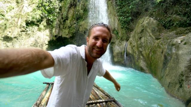 Hombre-joven-abrazando-a-bella-cascada-en-Filipinas