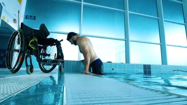 Disabled-man-gets-out-of-the-swimming-pool-Side-view