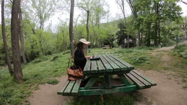 joven-y-hermosa-mujer-tocando-el-sintetizador-en-la-mesa-de-un-parque-Francia