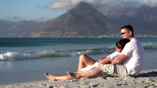 Couple-sitting-in-romantic-embrace-on-beach-Cape-Town-South-Africa