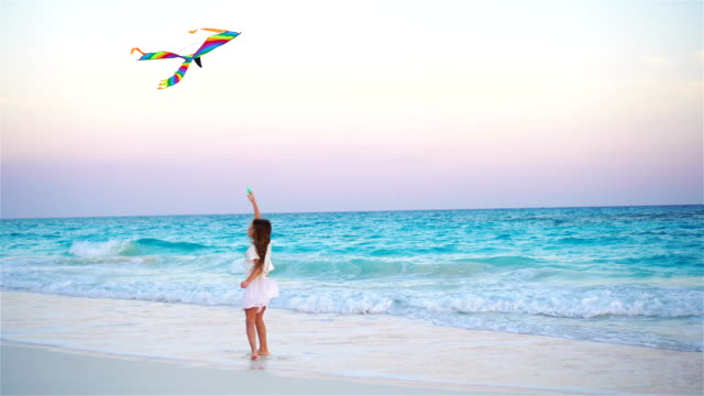 Niña-con-cometa-de-vuelo-en-playa-tropical-Niño-juega-en-la-costa-Niño-con-juguetes-para-la-playa-en-camara-lenta