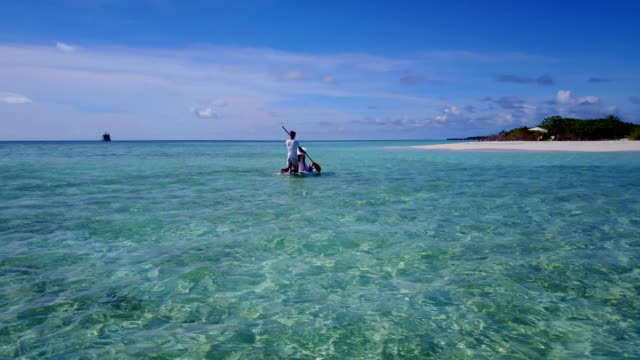v03861-Aerial-flying-drone-view-of-Maldives-white-sandy-beach-2-people-young-couple-man-woman-relaxing-on-paddleboard-on-sunny-tropical-paradise-island-with-aqua-blue-sky-sea-water-ocean-4k