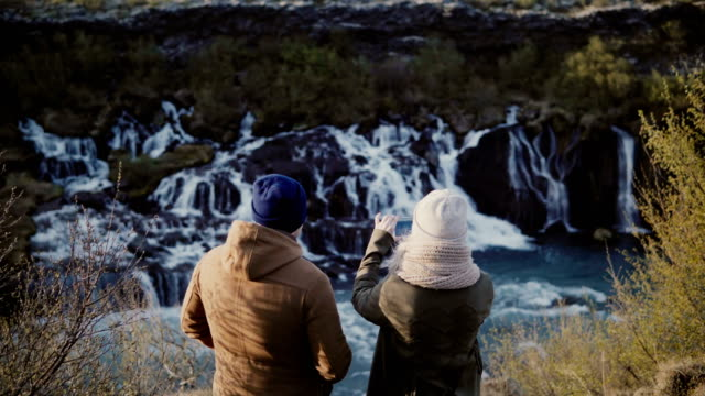 Back-view-of-young-traveling-couple-standing-in-mountains-near-the-waterfalls-in-Iceland-and-taking-photo-on-smartphone