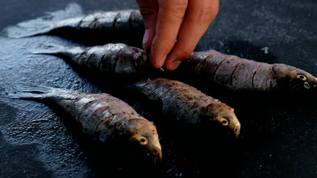 Man-salt-a-carp-fish-on-the-black-table-Cooking-fish-Hand-close-up-